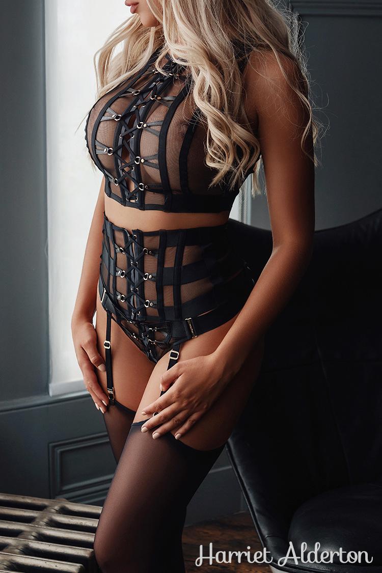 Busty blonde lady modelling black Honey Birdette lingerie.